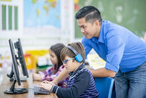 image of 2 children at a computer getting instruction from their teacher