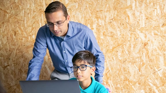 Programming instructor standing behind student with laptop