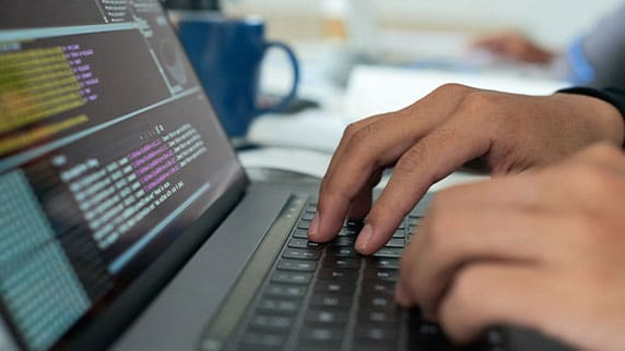 Image of hands on laptop with programming code on the screen