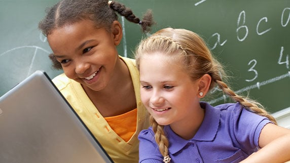 Picture of two children sitting behind a laptop smiling