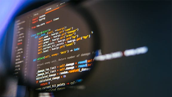 Image of programming code on a screen with a magnifying glass over it