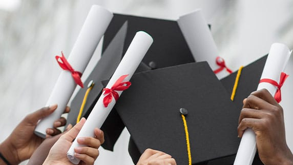 Picture of a group of graduates holding up degrees and graduation hats